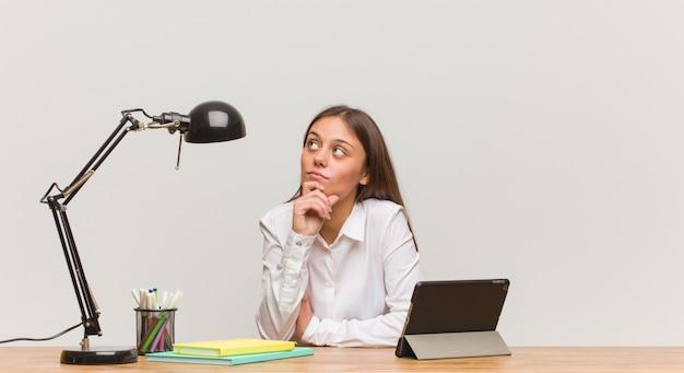 Junge studentenfrau, die an ihrem schreibtisch zweifelnd und verwirrt arbeitet