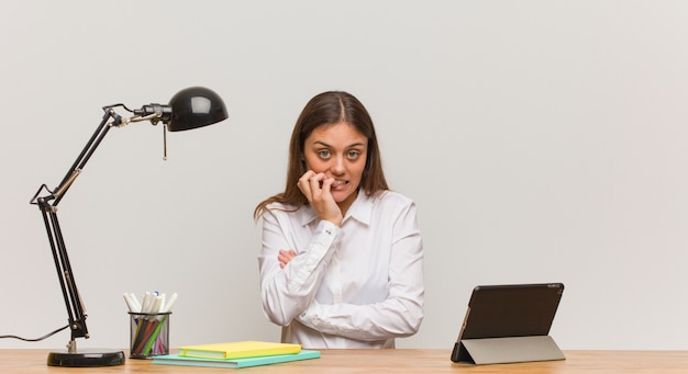 Junge studentenfrau, die an ihren beißenden nägeln des schreibtisches, nervös und sehr besorgt arbeitet