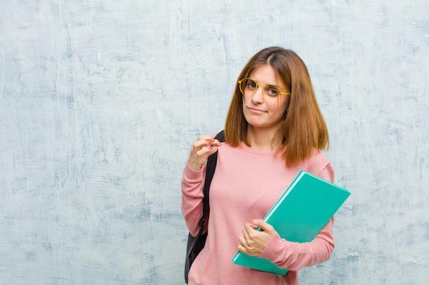 Junge studentenfrau, die arrogant, erfolgreich, positiv und stolz, zeigend auf selbst schaut