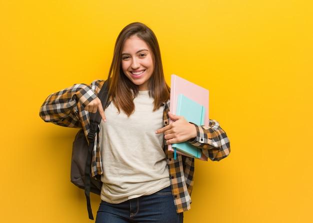 Junge studentenfrau, die auf die unterseite mit den fingern zeigt