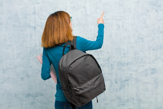 Junge studentenfrau, die auf gegenstand auf kopienraum, hintere ansicht gegen schmutzwandhintergrund steht und zeigt