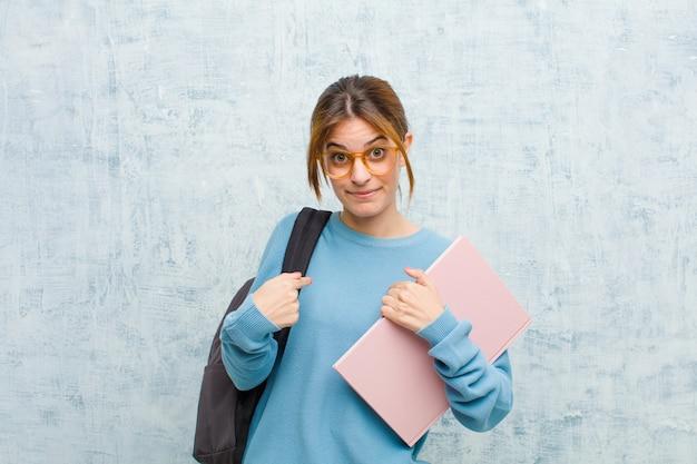 Junge studentenfrau, die auf selbst mit einem verwirrten und fragenden blick zeigt, entsetzt und überrascht, gewählt zu werden