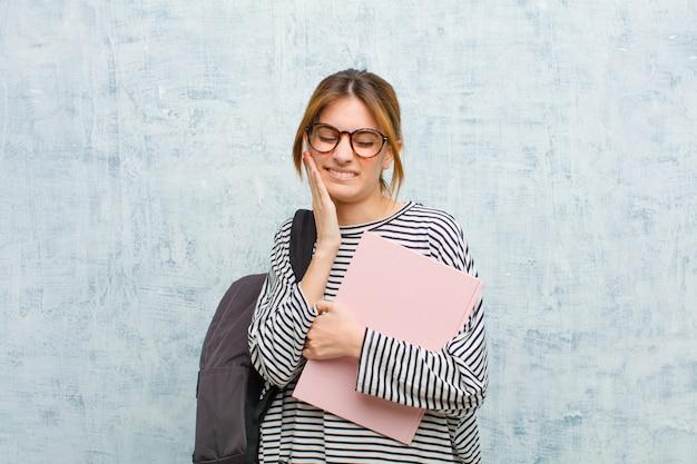 Junge studentenfrau, die backe hält und schmerzliche zahnschmerzen erleidet, krank, elend und unglücklich sich fühlt und nach einem zahnarzthintergrund sucht