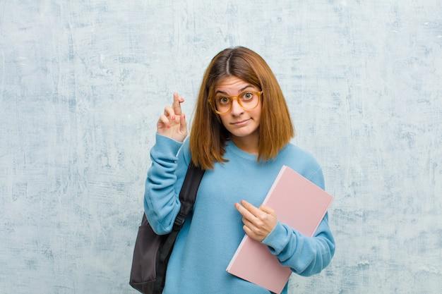 Junge studentenfrau, die besorgt finger kreuzt und auf gutes glück mit einem besorgten blick auf schmutzwand hofft