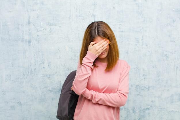 Junge studentenfrau, die betont, beschämt oder, mit kopfschmerzen, gesicht mit der hand gegen schmutzwand bedeckend gestört schaut