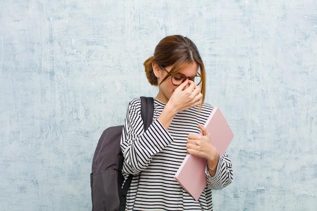 Junge studentenfrau, die betont, unglücklich und frustriert sich fühlt, stirn berührt und migräne von schweren kopfschmerzen gegen schmutz erleidet