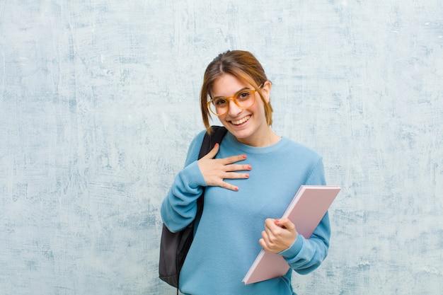 Junge studentenfrau, die das glückliche überraschte stolze und aufgeregte zeigen auf selbst schaut