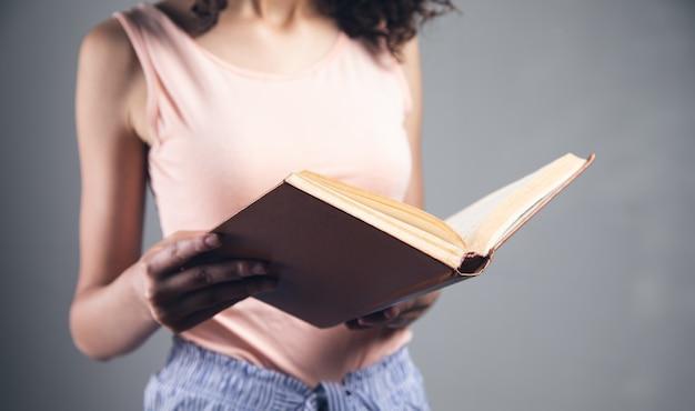 Junge studentenfrau, die ein buch liest.