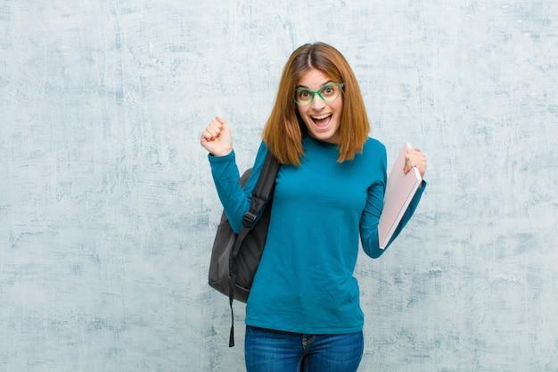 Junge studentenfrau, die entsetzt, aufgeregt und glücklich sich fühlt
