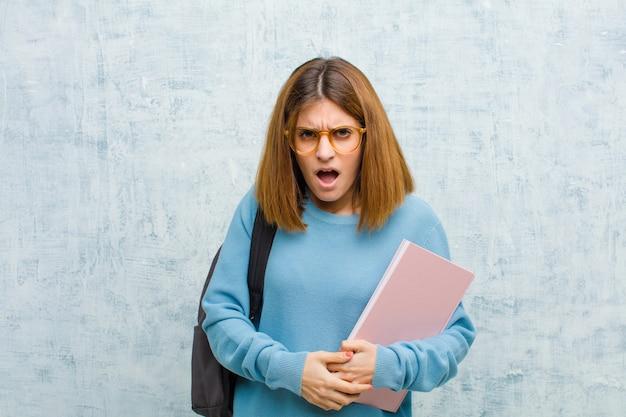 Junge studentenfrau, die entsetzt, verärgert, gestört oder enttäuscht, mit offenem mund und wütend gegen schmutz schaut