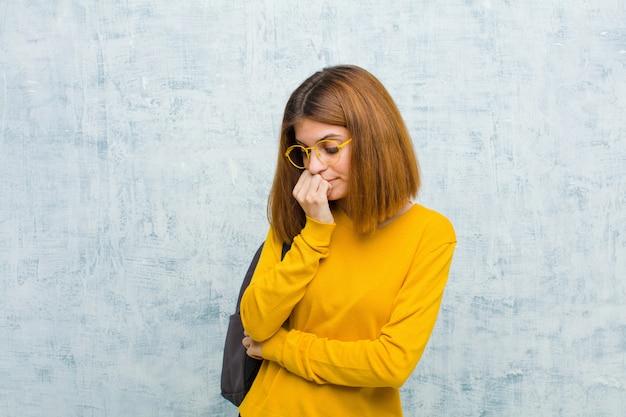 Junge studentenfrau, die ernst, durchdacht und betroffen sich fühlt und seitlich mit dem handgedrückten kinn gegen schmutzwand anstarrt