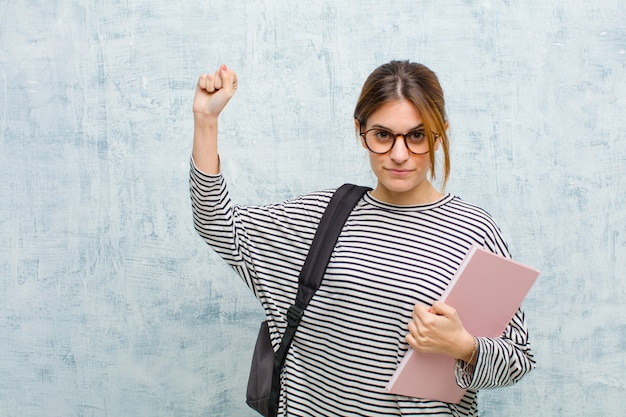 Junge studentenfrau, die ernst, stark und rebellisch sich fühlt, faust oben anhebt, für revolution protestiert oder kämpft