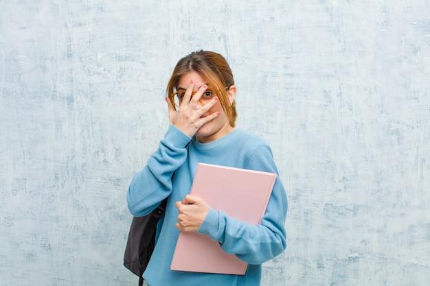 Junge studentenfrau, die erschrocken oder verlegen sich fühlt, mit den augen späht oder ausspioniert, die mit den händen halb bedeckt sind