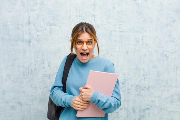 Junge studentenfrau, die erschrocken und entsetzt sich fühlt, wenn der breite mund in der überraschung gegen schmutzwandhintergrund offen ist