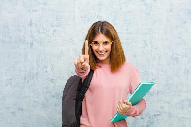 Junge studentenfrau, die freundlich lächelt und schaut, nummer eins oder zuerst mit der hand vorwärts zeigt und unten gegen schmutzwandhintergrund zählt