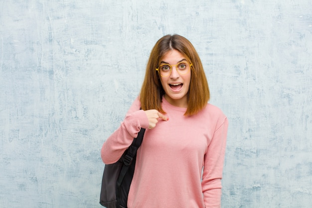 Junge studentenfrau, die glücklich, stolz und überrascht schaut und nett auf selbst zeigt, überzeugt und hoch sich fühlt