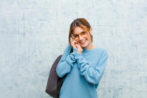 Junge studentenfrau, die in der liebe sich fühlt und nett entzückend und glücklich lächelt romantisch mit den händen nahe bei gesicht schaut