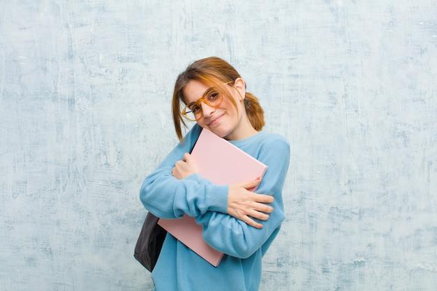 Junge studentenfrau, die in liebe glaubt, selbst lächelt, streichelt und umarmt, einzeln bleibt und egoistische und egozentrische schmutzwand ist