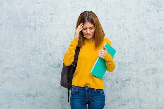 Junge studentenfrau, die konzentriert, durchdacht und angespornt schaut, mit den händen auf stirn gegen schmutzwandwand gedanklich löst und sich vorstellt