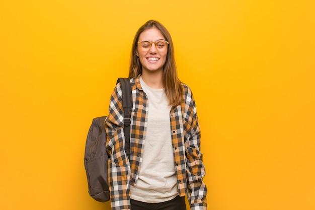 Junge studentenfrau, die, lustige, freundliche und sorglose geste blinzelt