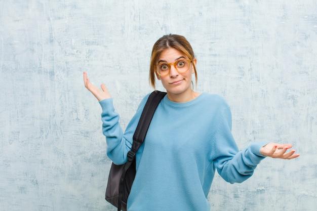 Junge studentenfrau, die mit einem stummen, verrückten, verwirrten, verwirrten ausdruck zuckt, gestört und gegen schmutzwand ahnungslos sich fühlt