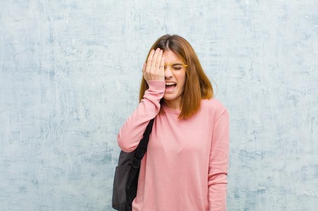 Junge studentenfrau, die, mit kopfschmerzen und einer hand bedeckt hälfte der gesichtsschmutzwand schläfrig, gelangweilt und gähnend schaut