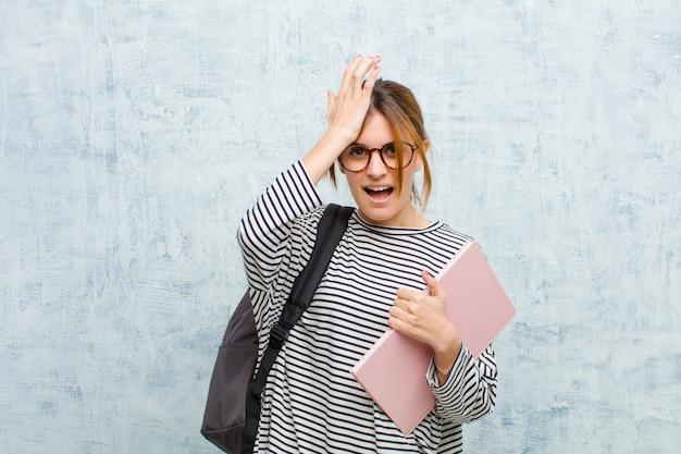 Junge studentenfrau, die palme zur stirn denkend anhebt, oops, nachdem ein dummer fehler gemacht worden ist oder sich erinnert worden ist und gegen schmutzwandhintergrund sich stumm gefühlt hat