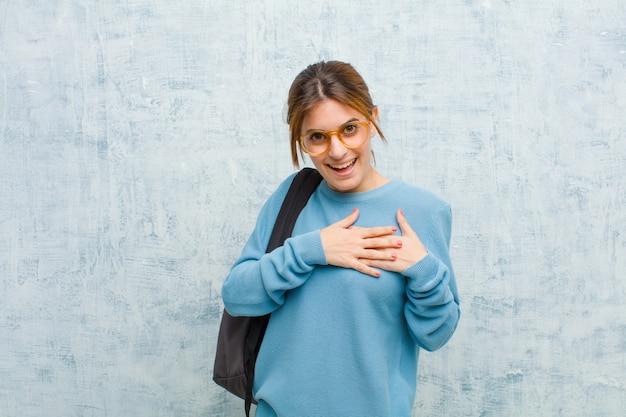 Junge studentenfrau, die romantisch, glücklich und in der liebe sich fühlt, nett lächelt und hände nah an herzen gegen schmutzwandhintergrund hält
