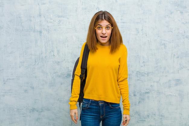 Junge studentenfrau, die sehr entsetzt schaut