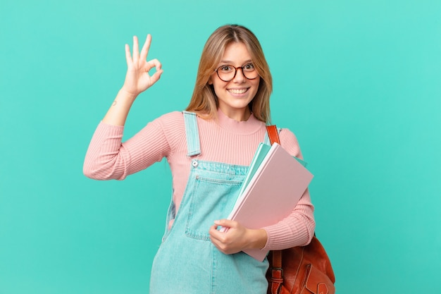 Junge studentenfrau, die sich glücklich fühlt und zustimmung mit okayer geste zeigt