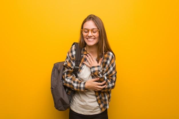 Junge studentenfrau, die spaß lacht und hat