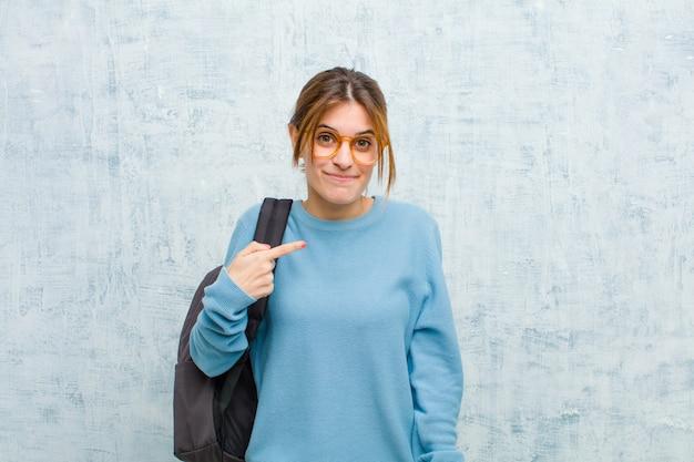 Junge studentenfrau, die stolz, überzeugt und glücklich schaut, auf selbst lächelt und zeigt oder nummer eins-zeichen macht