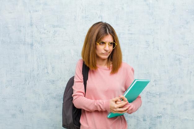 Junge studentenfrau, die traurig, verärgert oder verärgert sich fühlt und zur seite mit einer negativen haltung schaut und in der uneinigkeit die stirn runzelt