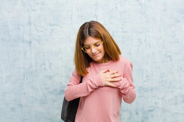 Junge studentenfrau, die traurig, verletzt und gebrochen schaut, beide hände nah an innerem hält, gegen schmutzwand schreit und niedergedrückt sich fühlt