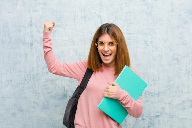 Junge studentenfrau, die triumphierend schreit und wie der aufgeregte, glückliche und überraschte sieger aussieht und gegen schmutzwandhintergrund feiert