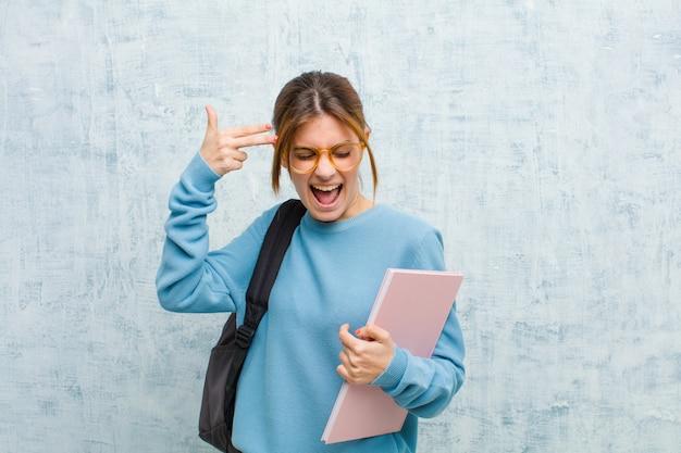 Junge studentenfrau, die unglücklich und, selbstmordgeste macht gewehrzeichen mit der hand betont schaut und zeigt auf hauptschmutzwand