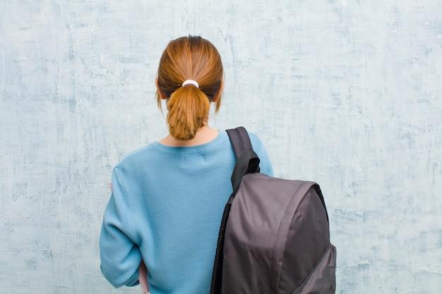Junge studentenfrau, die verwirrt oder voll oder die zweifel und fragen, sich wundernd, mit den händen auf hüften, hintere ansicht glaubt