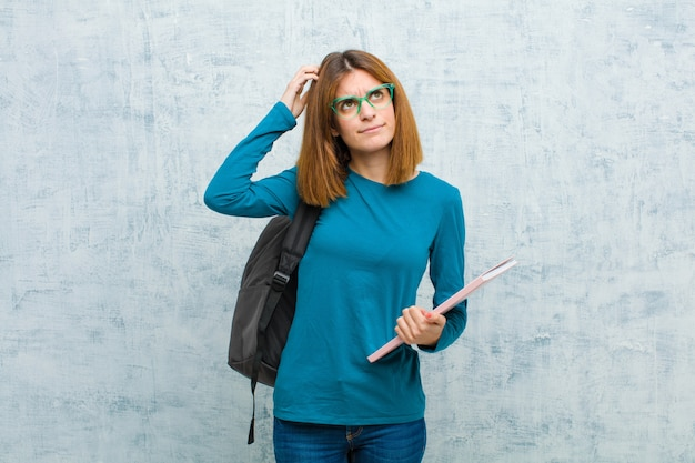 Junge studentenfrau, die verwirrt und verwirrt sich fühlt, kopf verkratzt und zur seite gegen schmutzwandhintergrund schaut