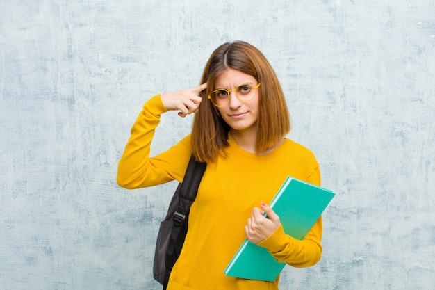 Junge studentenfrau, die verwirrt und verwirrt sich fühlt und zeigt, dass sie geisteskrank, verrückt oder aus ihrem sinneshintergrund heraus sind