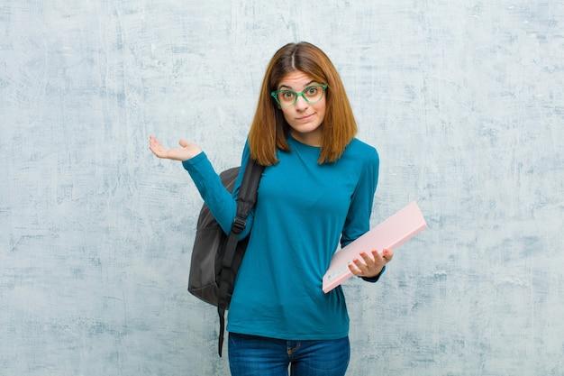 Junge studentenfrau, die verwirrt und verwirrt sich fühlt, verschiedene wahlen mit lustigem ausdruck gegen schmutzwandwand bezweifelt, belastet oder wählt