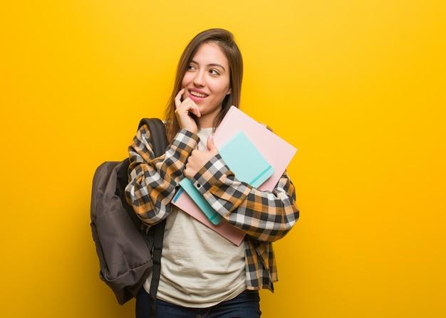 Junge studentenfrau entspannte sich das denken an etwas, das einen kopienraum betrachtet