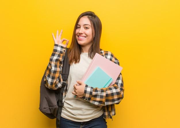Junge studentenfrau nett und überzeugt, okaygeste tuend
