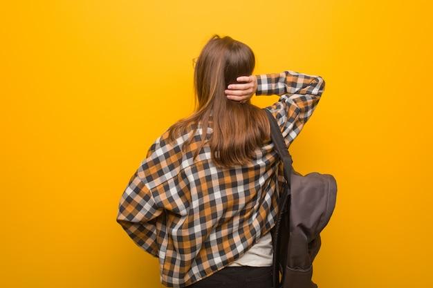 Junge studentenfrau von hinten, die an etwas denkt