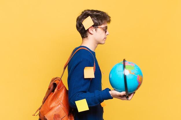 Junge studentenjunge auf der profilansicht, die den raum nach vorne kopieren, denken, sich vorstellen oder träumen möchte