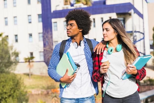 Junge studentenpaare, die bücher und die wegwerfkaffeetasse stehen gegen den campus weg schauen halten