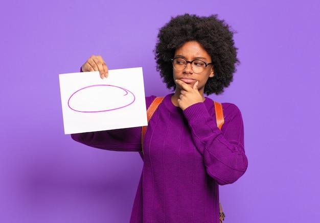 Junge studentin afro frau, die mit einem glücklichen, selbstbewussten ausdruck mit der hand am kinn lächelt, sich wundert und zur seite schaut