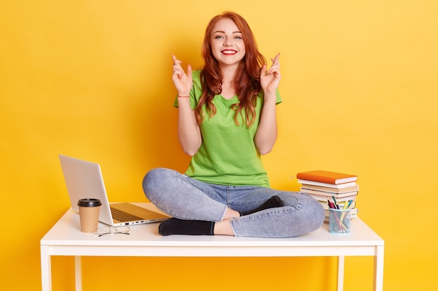 Junge studentin am arbeitsplatz mit laptop und büchern, mit gekreuzten fingern sitzend, wünscht am besten, mit gekreuzten beinen auf weißem tisch sitzend, schaut lächelnd direkt in die kamera.