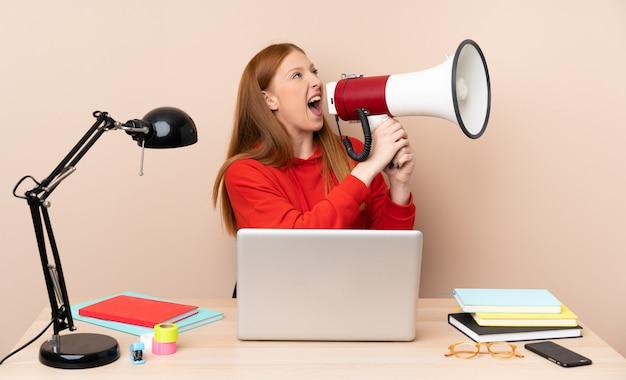 Junge studentin an einem arbeitsplatz mit einem laptop, der durch ein megaphon schreit