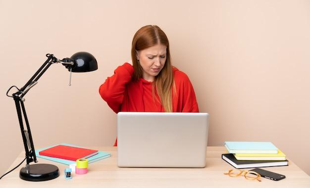 Junge studentin an einem arbeitsplatz mit einem laptop mit nackenschmerzen