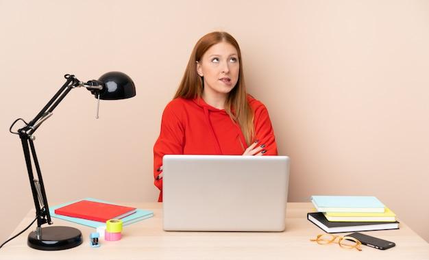 Junge studentin an einem arbeitsplatz mit einem laptop mit verwirrendem gesichtsausdruck